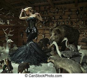 Mujer sensual en una habitación cerrada llena de animales salvajes