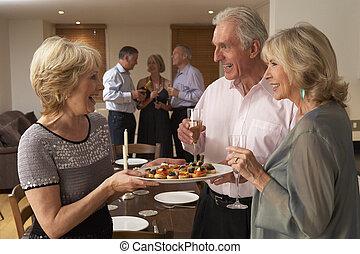 Mujer sirviendo aperitivos a sus invitados en una cena