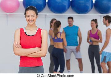 Mujer sonriente con amigos de fondo en el estudio de fitness