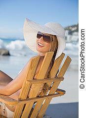 Mujer sonriente con sombrero de paja relajándose en la silla de la playa