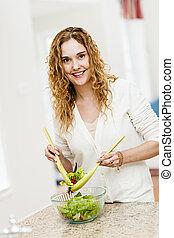 Mujer sonriente lanzando ensalada en la cocina