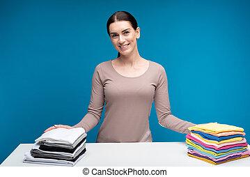 Mujer sonriente mostrando ropa limpia