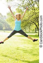 Mujer sonriente saltando en el parque