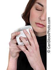 Mujer sosteniendo taza de café a la cara