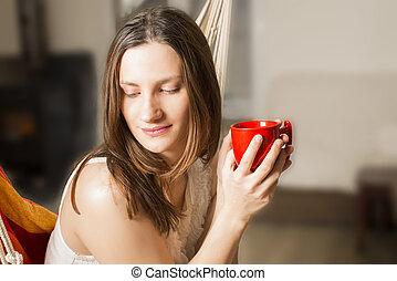 Mujer sosteniendo taza roja de café