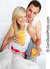 Mujer sosteniendo un vaso de jugo de naranja