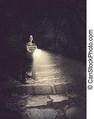 Mujer sosteniendo una Biblia resplandeciente en el bosque