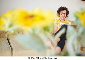 mujer, tableta, digital, sentado, utilizar, sofá