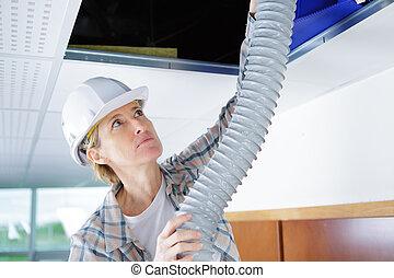 Mujer trabajadora que encaja con el sistema de ventilación en el techo de los edificios