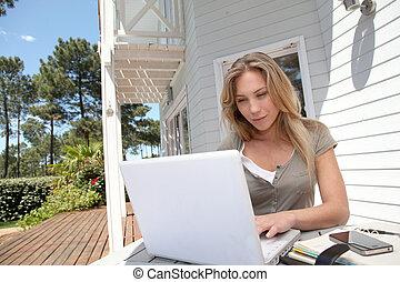 Mujer trabajando en casa en computadora portátil