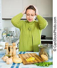 Mujer triste en la cocina
