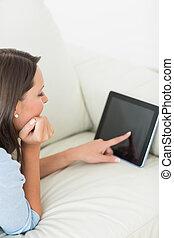 Mujer tumbada en el sofá usando tablillas