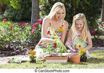 Mujer y chica, madre e hija, jardinería plantando flores