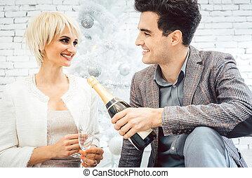 Mujer y hombre bajo el árbol de Navidad blanco con vino brillante