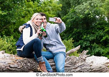 Mujer y hombre bebiendo cerveza tomando selfie mientras camina