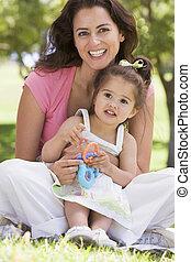 Mujer y joven sentadas al aire libre con juguetes sonriendo