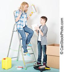 Mujer y niño pintando pared