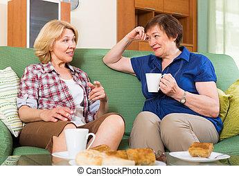 Mujeres ancianas en la mesa con té
