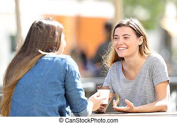 Mujeres felices hablando sentados en un parque