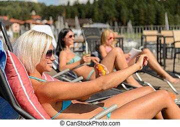 Mujeres jóvenes tumbadas en la silla de cubierta aplicando protector solar