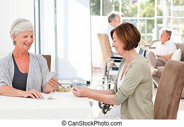 Mujeres mayores jugando a las cartas mientras sus maridos hablan