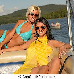Mujeres sonrientes tomando el sol en el barco