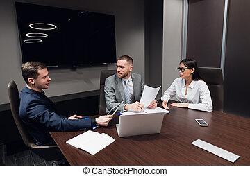 Negocios de inicio, gente de negocios creativa de diferentes edades y razas se reúnen en la sala de reuniones en el interior de la oficina moderna oscura, discutiendo vivo