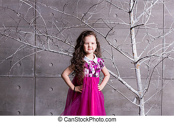 Niña morena de 5 años con un vestido rosa. En la habitación gris de vacaciones con árbol.