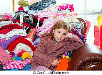 Niña rubia sentada en un sofá de ropa sucia