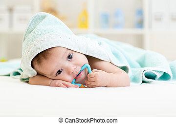 Niño bajo la toalla después de bañarse en casa