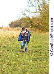 Niño chapoteando en un charco en el campo