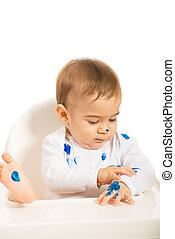 Niño con pintura azul en las manos