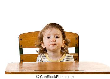 Niño de educación temprana sentado en el escritorio de la escuela