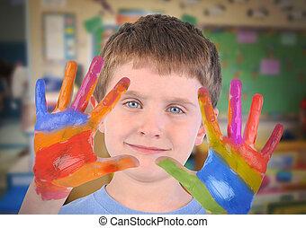 Niño de la escuela de arte con las manos pintadas