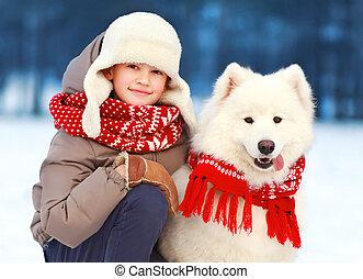 Niño de Navidad Retrato caminando con perro blanco Samoyed en el día de invierno
