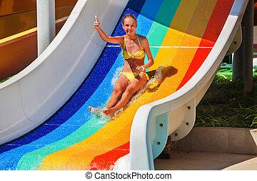 Niño en tobogán de agua en Aquapark mostrar pulgar arriba.