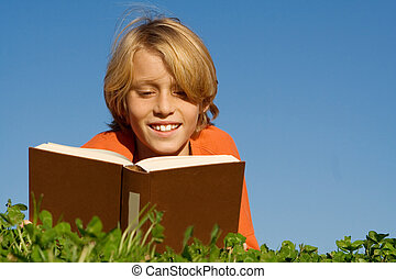 Niño feliz, leyendo libros al aire libre,