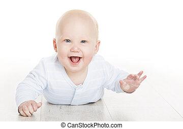 Niño feliz, niño pequeño acostado en suelo blanco, hermoso niño de seis meses aislado sobre fondo blanco