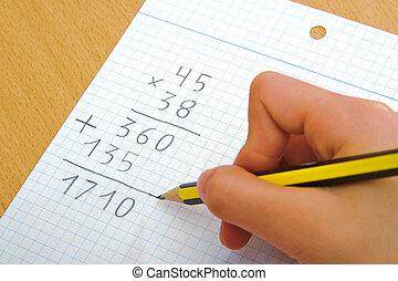 Niño haciendo una multiplicación de matemáticas en la escuela.