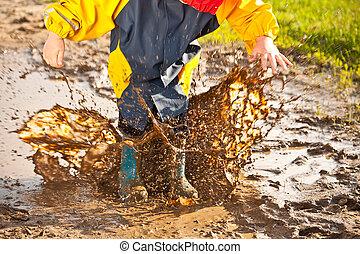 Niño salpicando en lodo