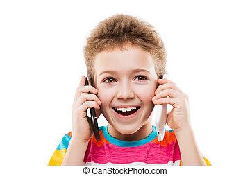 Niño sonriente hablando con dos móviles o teléfonos inteligentes