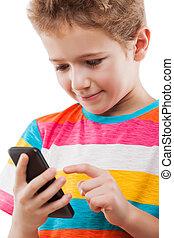 Niño sonriente hablando por teléfono móvil o por teléfono