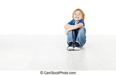 Niño sonriente sentado y mirando cámara