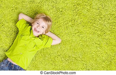 Niño tendido sobre la alfombra verde. Chico sonriente feliz, chico de cinco años, vista superior
