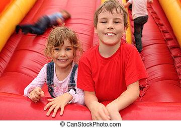 Niño y niña acostados en el tobogán inflable rojo, sonriendo y mirando a la cámara