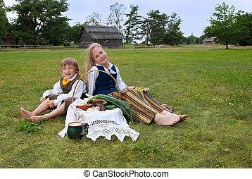 Niño y niña sentados en un césped con ropa latviana nacional