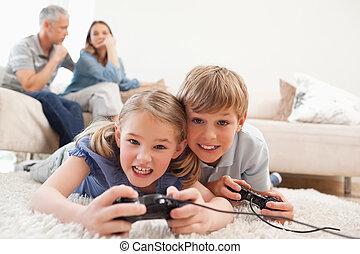 Niños alegres jugando videojuegos con sus padres en el fondo de una sala de estar