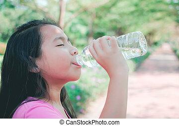 Niños bebiendo agua en el parque.
