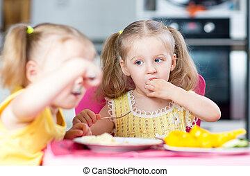 Niños comiendo en la guardería o en casa