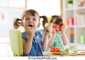 Niños comiendo vegetales en la guardería o en casa
